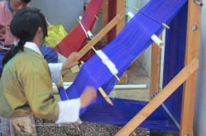 A young Bhutanese woman learning to weave.